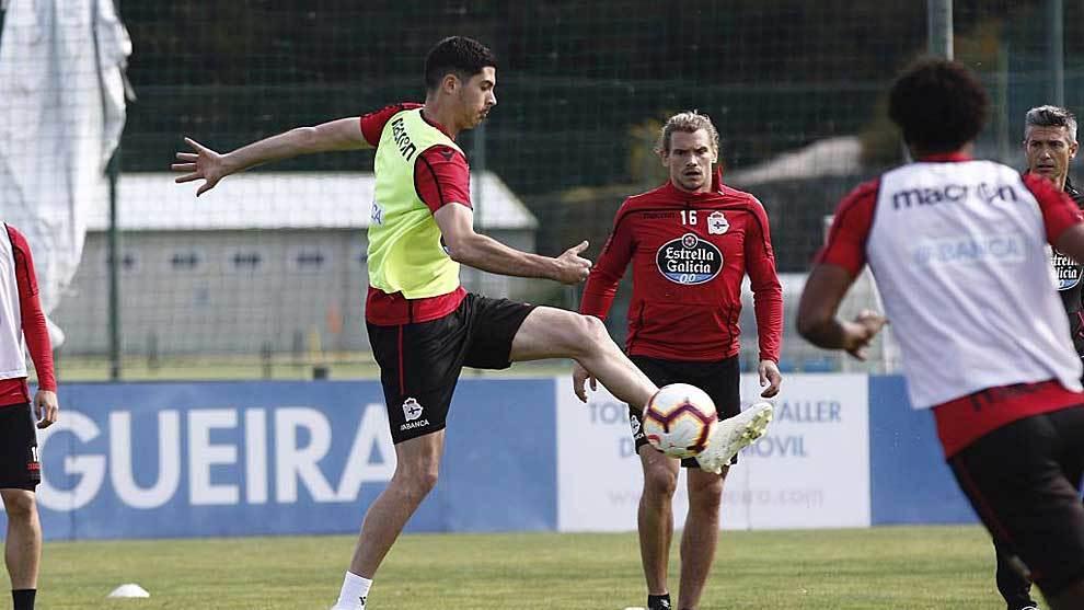 Carlos Fernández controla el balón ante la mirada de Martí en un...
