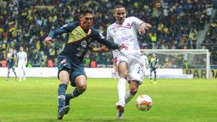 Edson Álvarez y Diego Chávez luchan por el balón.