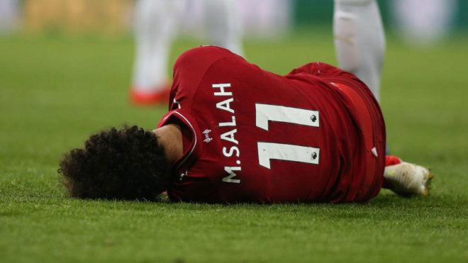 Salah se duele sobre el césped.