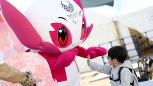 Un niño saluda a una de las mascotas de los Juegos