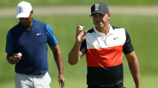 Brooks Koepka agradece los aplausos, con Tiger Woods a su lado.