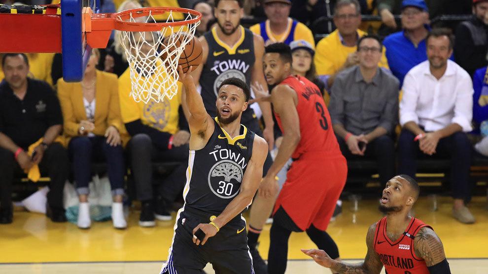 Curry anota ante la mirada de Damian Lillard