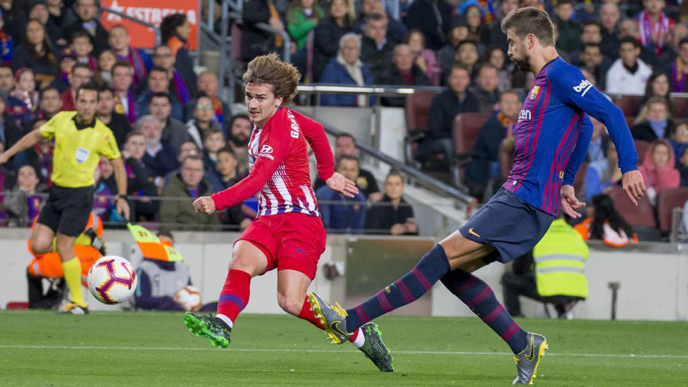 Antoine Griezmann getting a shot away with Gerard Piqué in close...