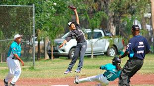 Niños jugando durante una liga telmex telcel de béisbol.