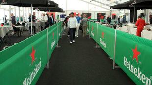 Un golfista atraviesa en mitad de recorrido la carpa de Heineken