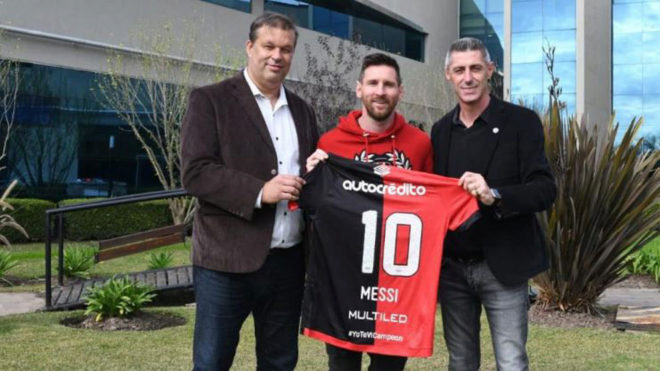 Lionel Messi holding up the Newell's Old Boys shirt with his name and...