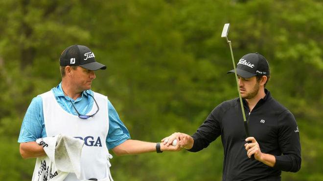 El caddie de Patrick Cantlay limpia su bola en el último PGA...