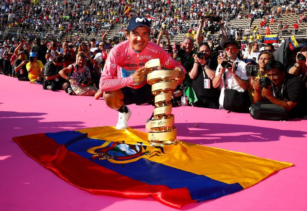 "TOPSHOT - Overall race winner Team <HIT>Movistar</HIT> rider Ecuadors Richard Carapaz poses with the ""Never ending trophy"" (Trofeo Senza Fine) by Ecuadors flag during podium ceremonies in the Verona arena, after the final stage of the 102nd Giro dItalia - Tour of Italy - cycle race, a 17km individual time-trial in Verona on June 2, 2019. (Photo by Luk BENIES / AFP)"