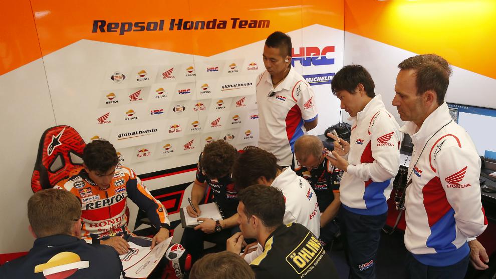Márquez, sentado en su box, con Puig a la derecha.