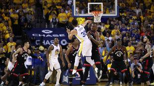 Stephen Curry anota ante Ibaka con los Raptors mirando el lanzamiento