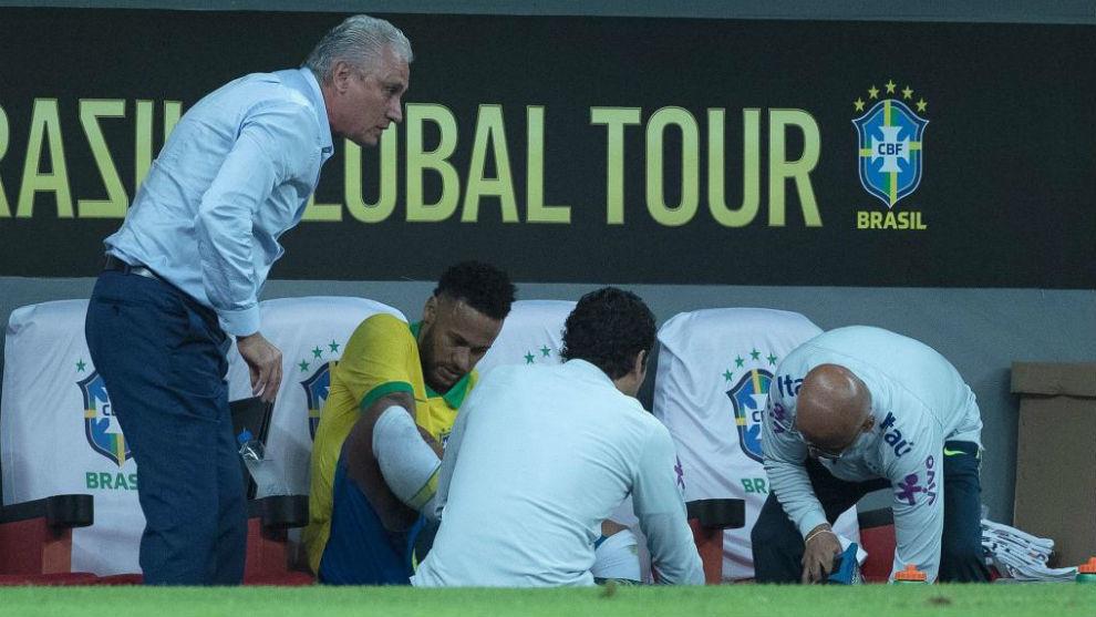 Neymar es atendido por los médicos de la selección brasileña tras...