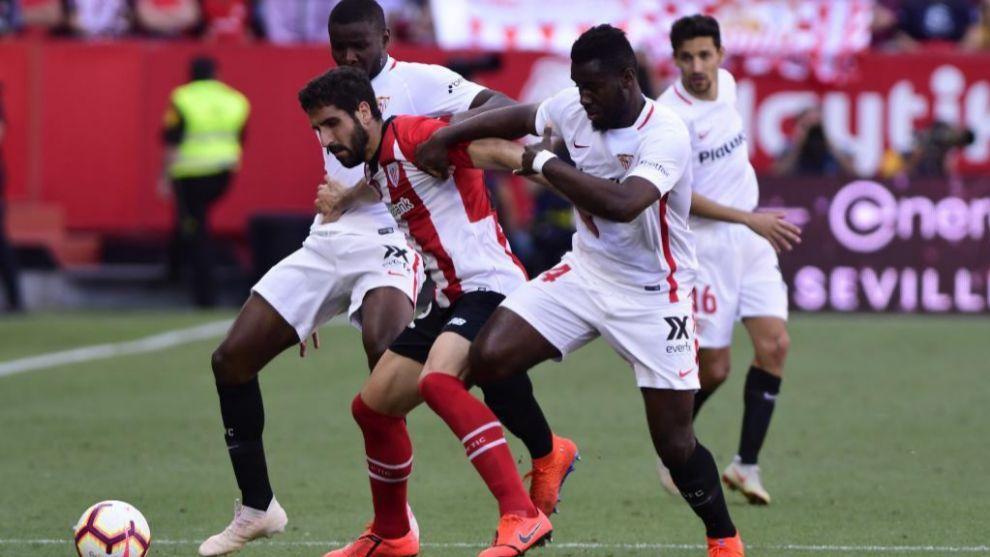 Raúl García, entre dos jugadores del Sevilla en el último partido...