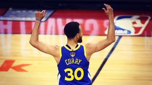 Stephen Curry alza los brazos para celebrar el triunfo de Warriors en...
