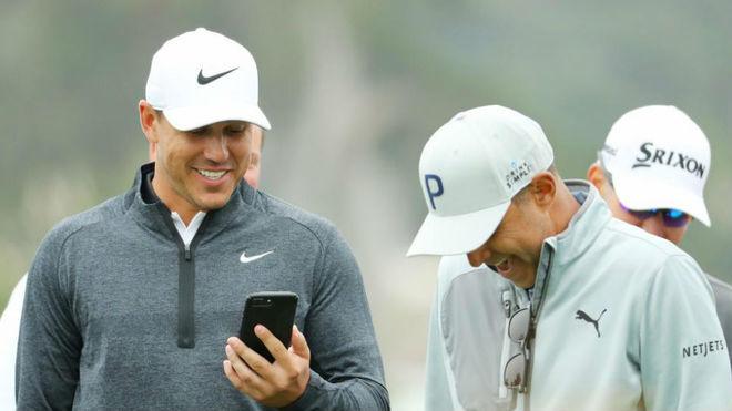 Brooks Koepka (29) mira su móvil durante la ronda de prácticas