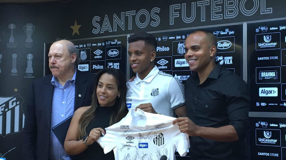 Rodrygo (18) with his parents and Santos' president during his...