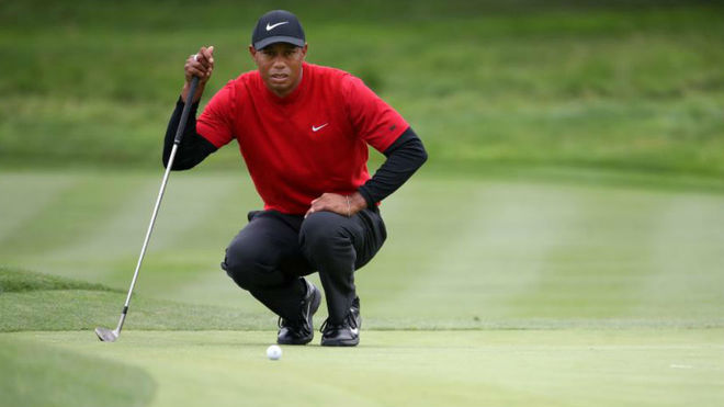 Tiger Woods se dispone a leer un putt.