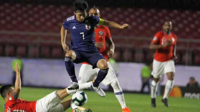 Gaku Shibasaki disputa un baló con Alexis Sánchez en el partido...