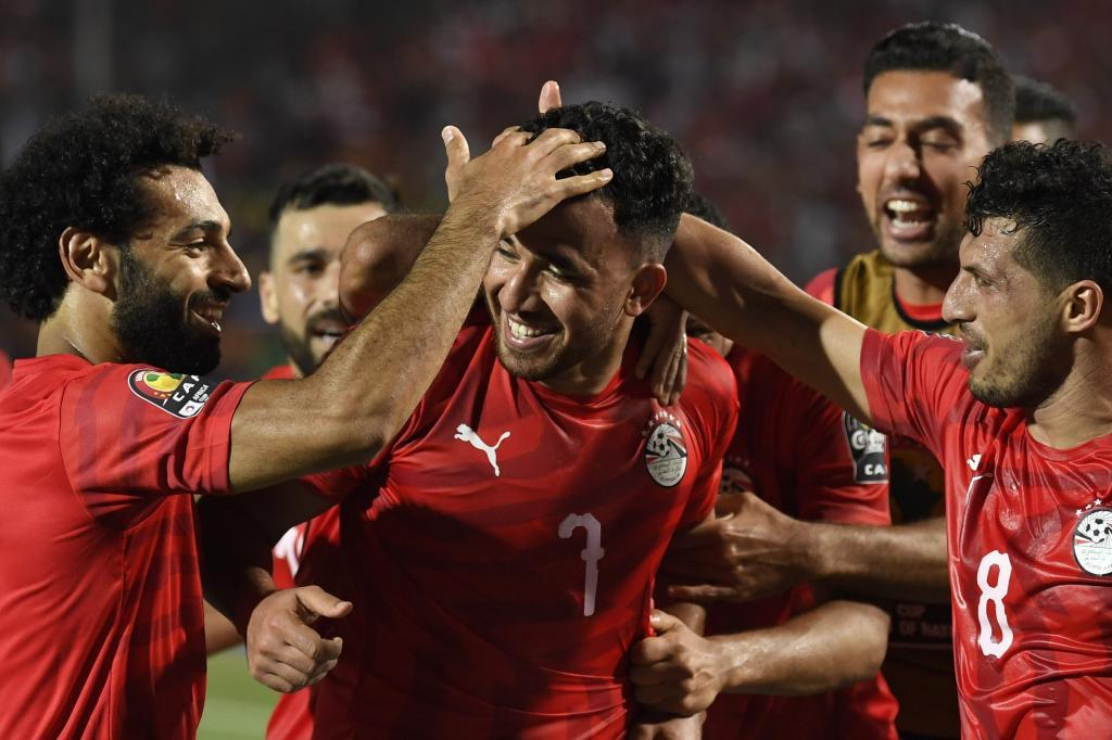 Egypts forward Mohamed <HIT>Salah</HIT> (L) and Egypts midfielder Tarek Hamed (R) congratulate Egypts midfielder Mahmoud Trezeguet Hassan (C) on his goal during the 2019 Africa Cup of Nations (CAN) football match between Egypt and Zimbabwe at Cairo International Stadium on June 21, 2019. (Photo by Khaled DESOUKI / AFP)