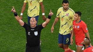 El argentino Pitana hace el gesto del VAR durante el Colombia-Chile