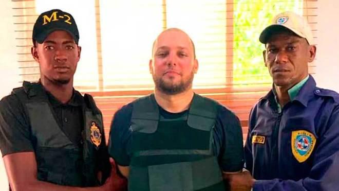 Agentes de la policía con el supuesto autor intelectual del atentado...