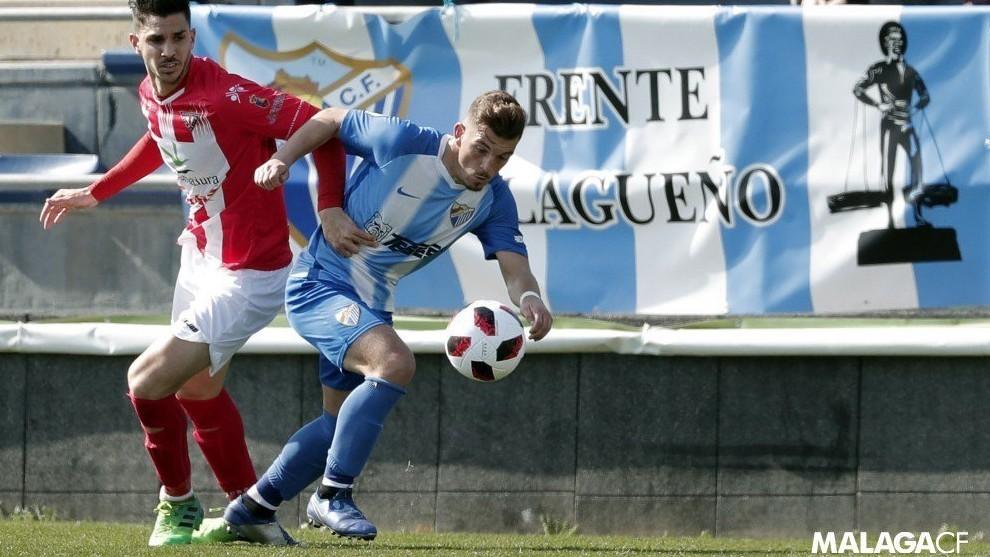 Un futbolista del Atlético Malagueño luchando por el balón