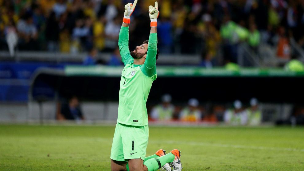 Alisson prays before a match.