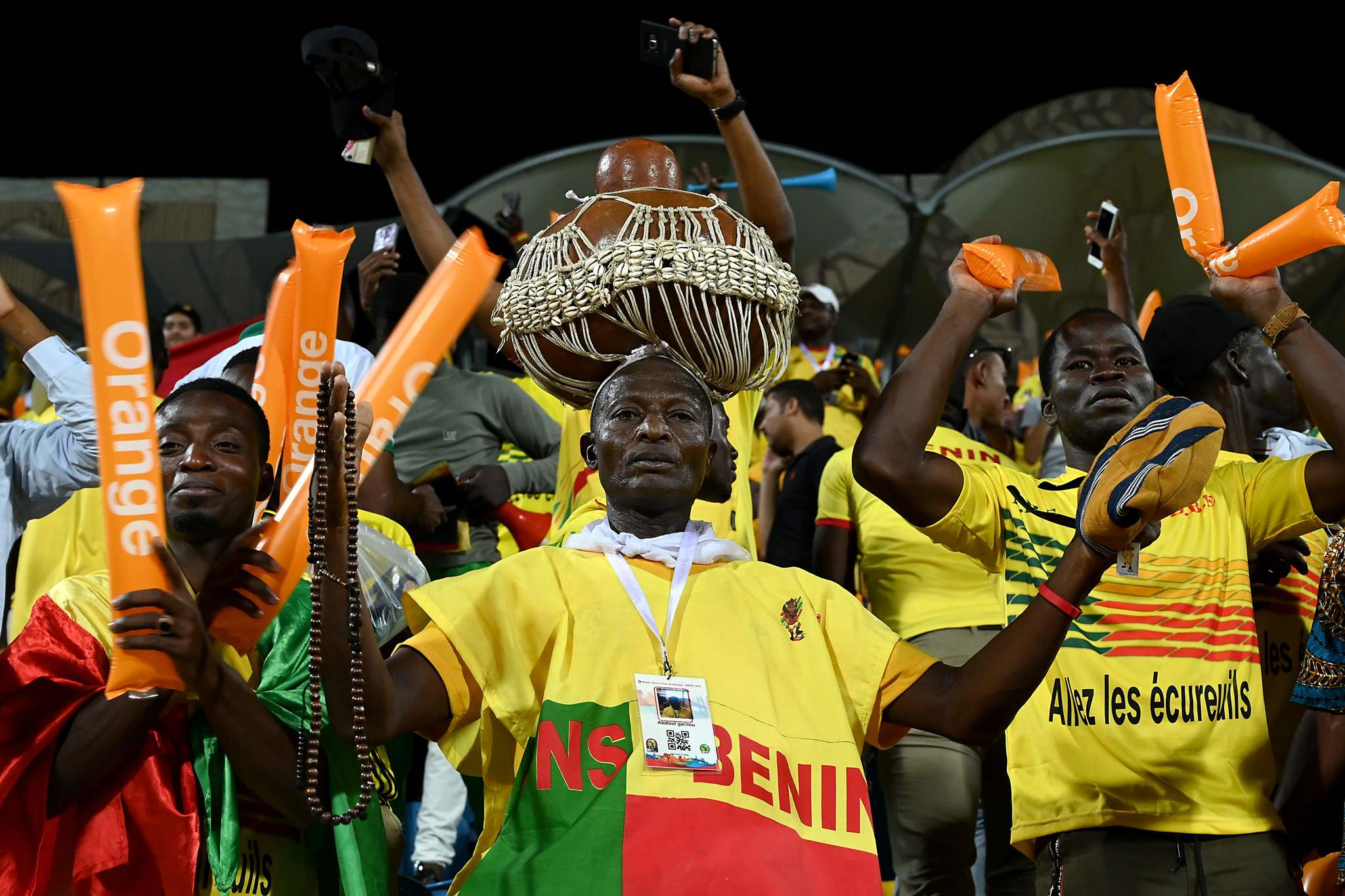 <HIT>Benin</HIT><HIT>fans</HIT> celebrate after qualifying for the round of 16 during the 2019 Africa Cup of Nations (CAN) Group F football match between <HIT>Benin</HIT> and Cameroon at the Ismailia Stadium in the north-eastern Egyptian city on July 2, 2019. (Photo by OZAN KOSE / AFP)