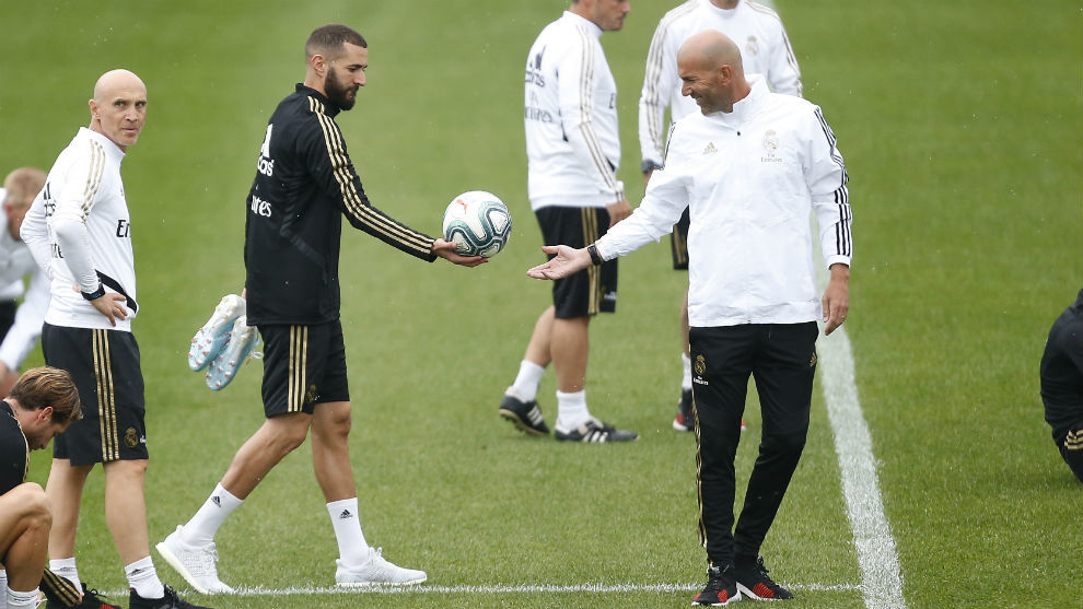 Karim Benzema hands the ball to Zinedine Zidane during Thursday's...