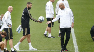 Benzema entrega una pelota a Zidne en el entrenamiento de ayer.