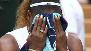 Serena Williams covers her face with a towel.