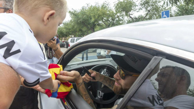 Nicolas Otamendi signing a scarf during his time as a Valencia player.
