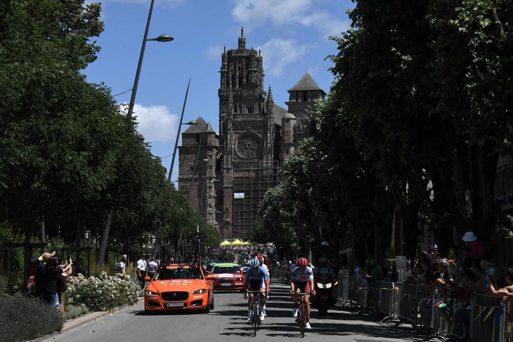 Denmarks Mads Schmidt (L), Frances Anthony Turgis (L) and cyclists ride in a breakaway with the cathedral of Rodez in background during the tenth stage of the 106th edition of the <HIT>Tour</HIT> de France cycling race between Saint-Flour and Albi, in Rodez, southern France, on July 15, 2019. (Photo by JEFF PACHOUD / AFP)