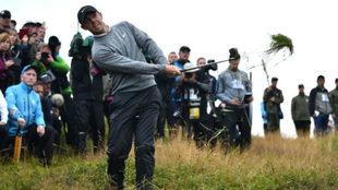 Rory McIlroy juega desde la hierba alta un golpe.