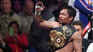 Pacquiao saluda con su cinturón de supercampeón de la WBA.