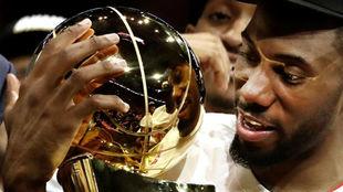 Kawhi Leonard junto al título de campeones de la NBA