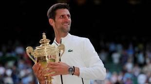 Novak Djokovic besa el trofeo de ganador de Wimbledon 2019.