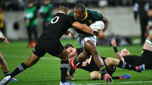 Makazole Mapimpi trata de evitar el placaje de Richie Mo'unga.