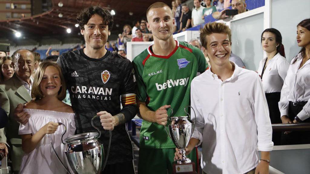 Cristian y Ely posan con los trofeos y con los nietos de Carlos...