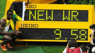 Usain Bolt posa con el electrónico que marca 9.58 como récord del...