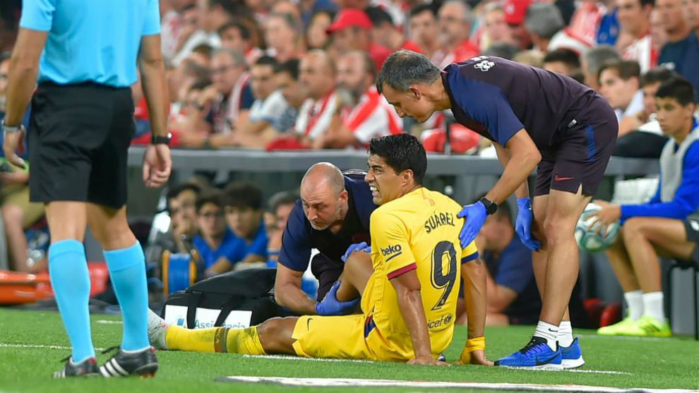 Luis Suárez atendido en la banda de San Mamés tras lesionarse anoche