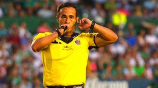 El árbitro Jorge Isaác Rojas señalando revisión.