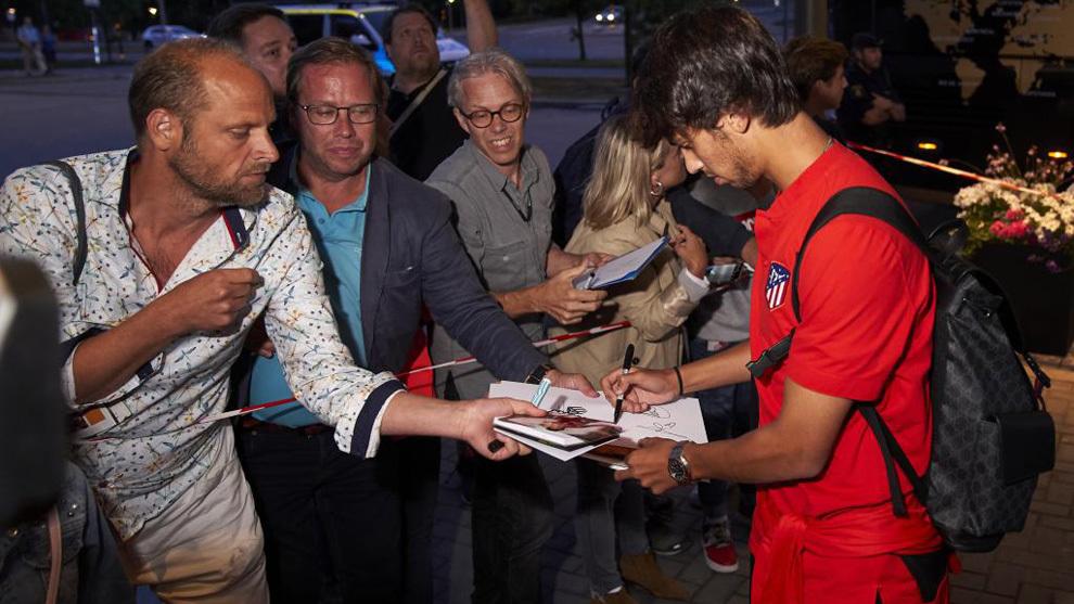 Joao Félix firma autógrafos a unos aficionados.