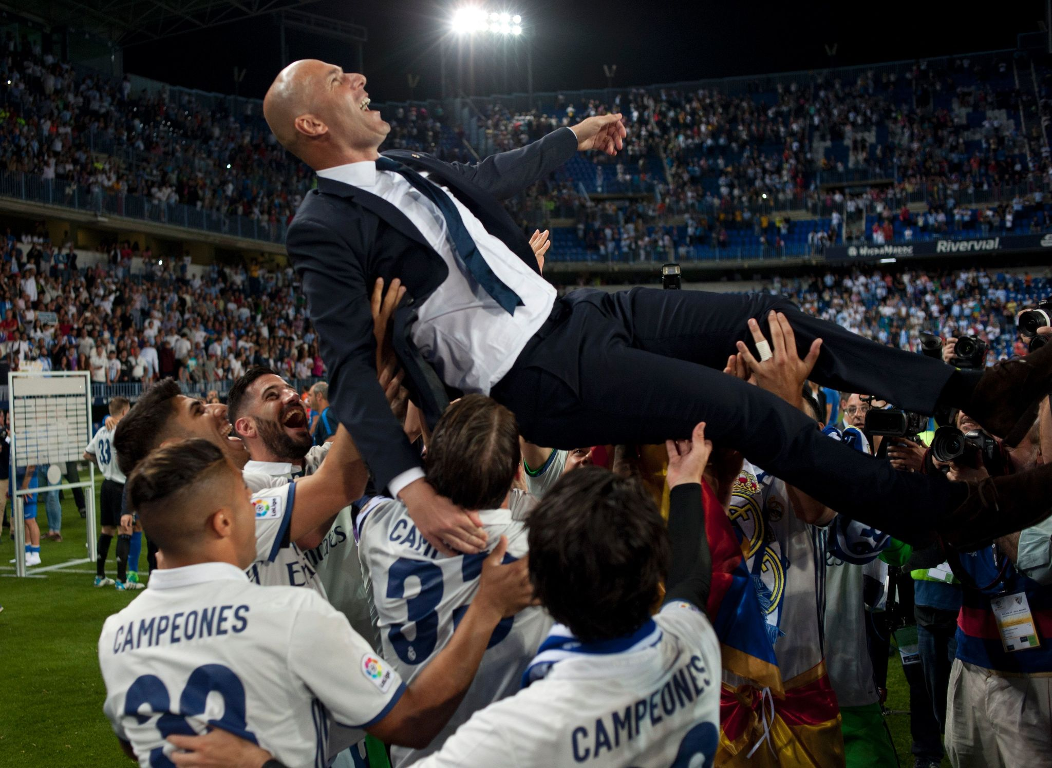 Real Madrids French head coach Zinedine <HIT>Zidane</HIT> is tossed by players at the end of the Spanish league football match <HIT>Malaga</HIT> CF vs Real Madrid at La Rosaleda stadium in <HIT>Malaga</HIT> on May 21, <HIT>2017</HIT>. Real Madrid won their 33rd La Liga title and first for five years as Cristiano Ronaldos 40th goal of the season helped seal a 2-0 win at <HIT>Malaga</HIT> today. / AFP PHOTO / SERGIO CAMACHO