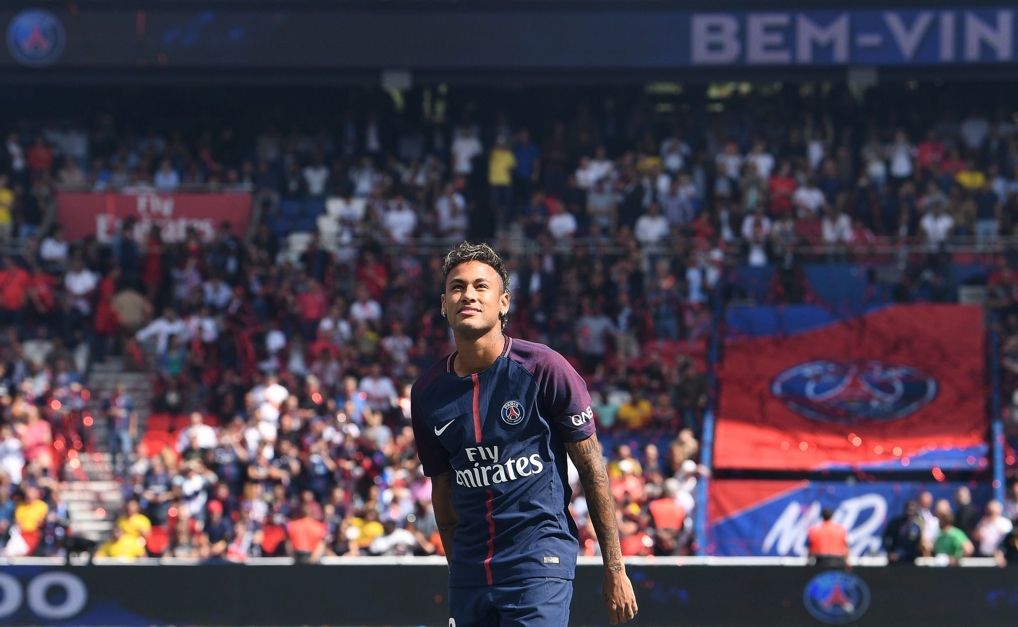 Paris Saint-Germains Brazilian forward <HIT>Neymar</HIT> looks on during his presentation to the fans at the Parc des Princes stadium in Paris on August 5, 2017. Brazil superstar <HIT>Neymar</HIT> will watch from the stands as Paris Saint-Germain open their season on August 5, 2017, but the French club have already clawed back around a million euros on their world record investment. <HIT>Neymar</HIT>, who signed from <HIT>Barcelona</HIT> for a mind-boggling 222 million euros ($264 million), is presented to the <HIT>PSG</HIT> support prior to his new teams first game of the Ligue 1 campaign against promoted Amiens. / AFP PHOTO / ALAIN JOCARD