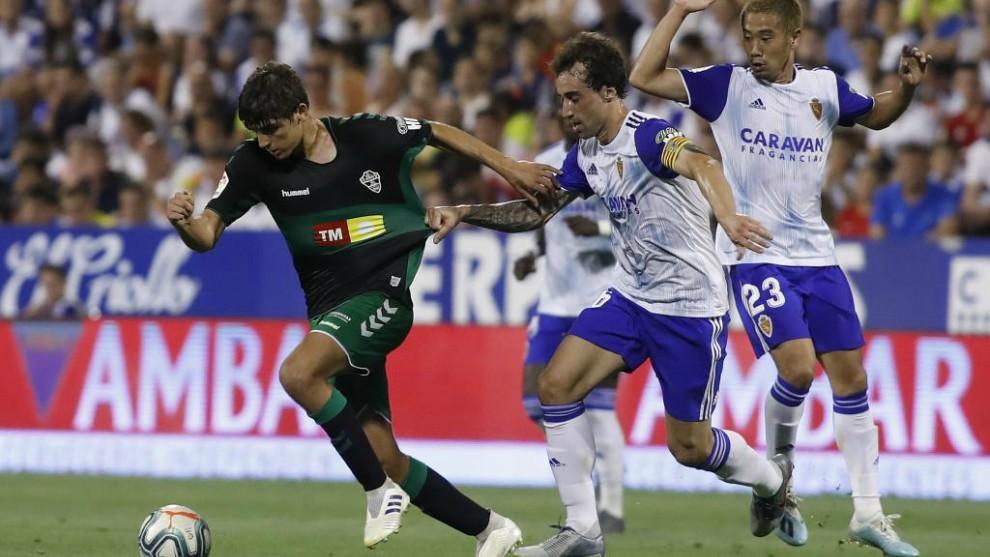 Gonzalo Villar, con el balón, es agarrado por Eguaras