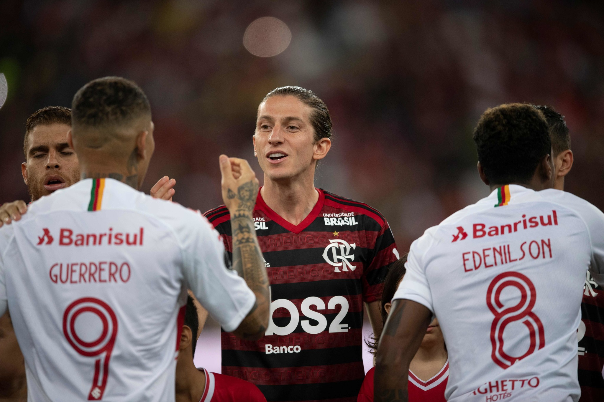 Brazils Flamengo team player <HIT>Filipe</HIT><HIT>Luis</HIT> (C) greets Brazils Internacional player Paolo Guerrero (L) during a 2019 Copa Libertadores football match at the Maracana stadium in Rio de Janeiro, Brazil, on August 21, 2019. (Photo by MAURO PIMENTEL / AFP)