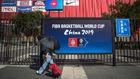 Una persona pasa ante un cartel del Mundial de baloncesto.
