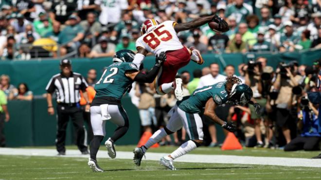 Vernon Davis salta sobre los defensores de los Eagles para firmar el...
