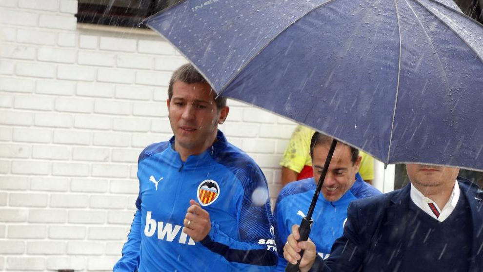 Albert Celades under an umbrella at Valencia's training ground.