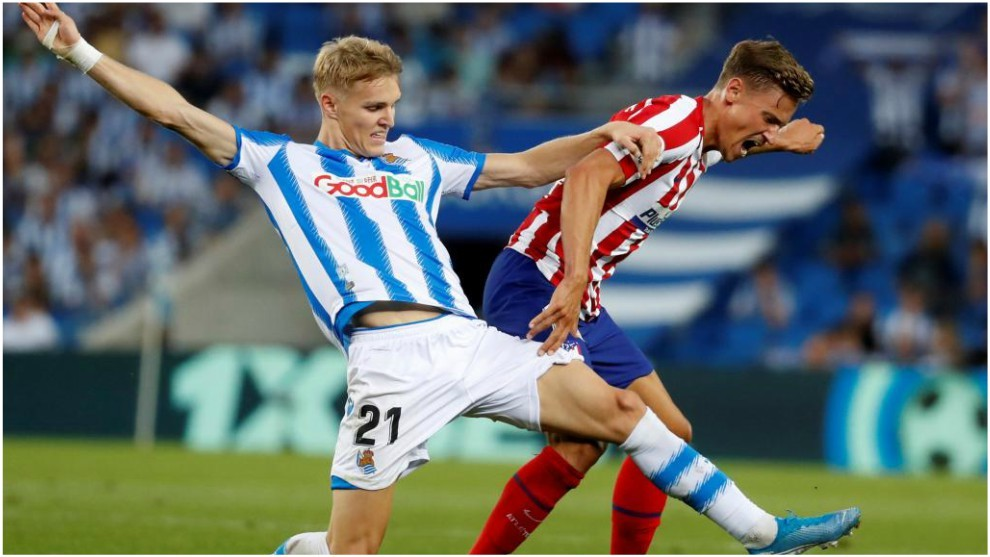 Martin Odegaard challenging for the ball with Marcos Llorente.